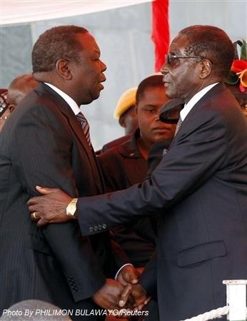 Zimbabwean President Robert Mugabe (R) greets Zimbabwean Prime Minister Morgan Tsvangirai